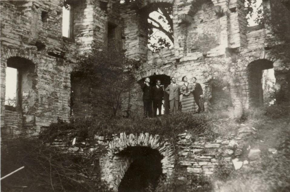 Eine Besuchergruppe betrachtet die Ruine des Herrenhause (ca. 1930).