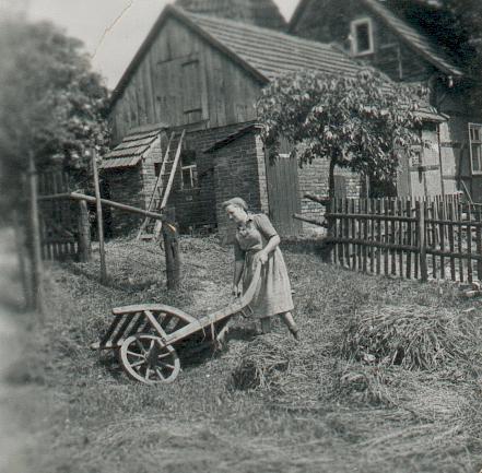 Arbeitsmaid mit Karre (ca. 1942). Im Hintergrund ist das Torhaus und das Dach des Torturmes zu erkennen.