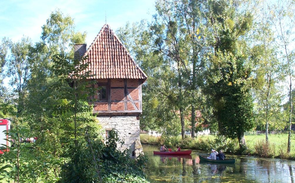 Blick auf den Ostturm und dem Burggraben mit Paddelbooten.